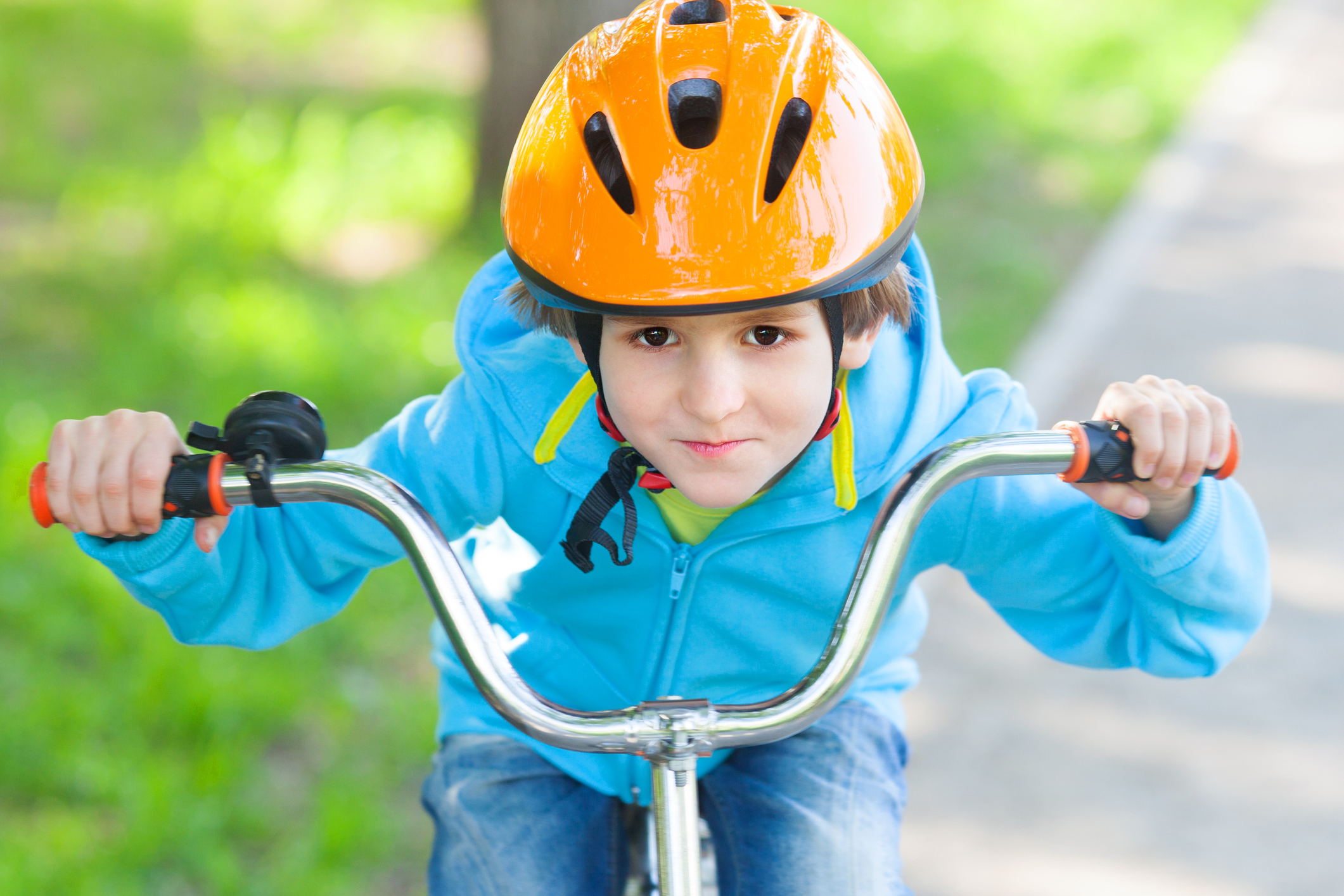 The small boy in blue fleece jacket ride a cycle in park at summer time